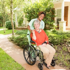 Caregiver assisting elderly woman in wheelchair