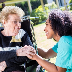 Healthcare service woman assists woman in wheelchair